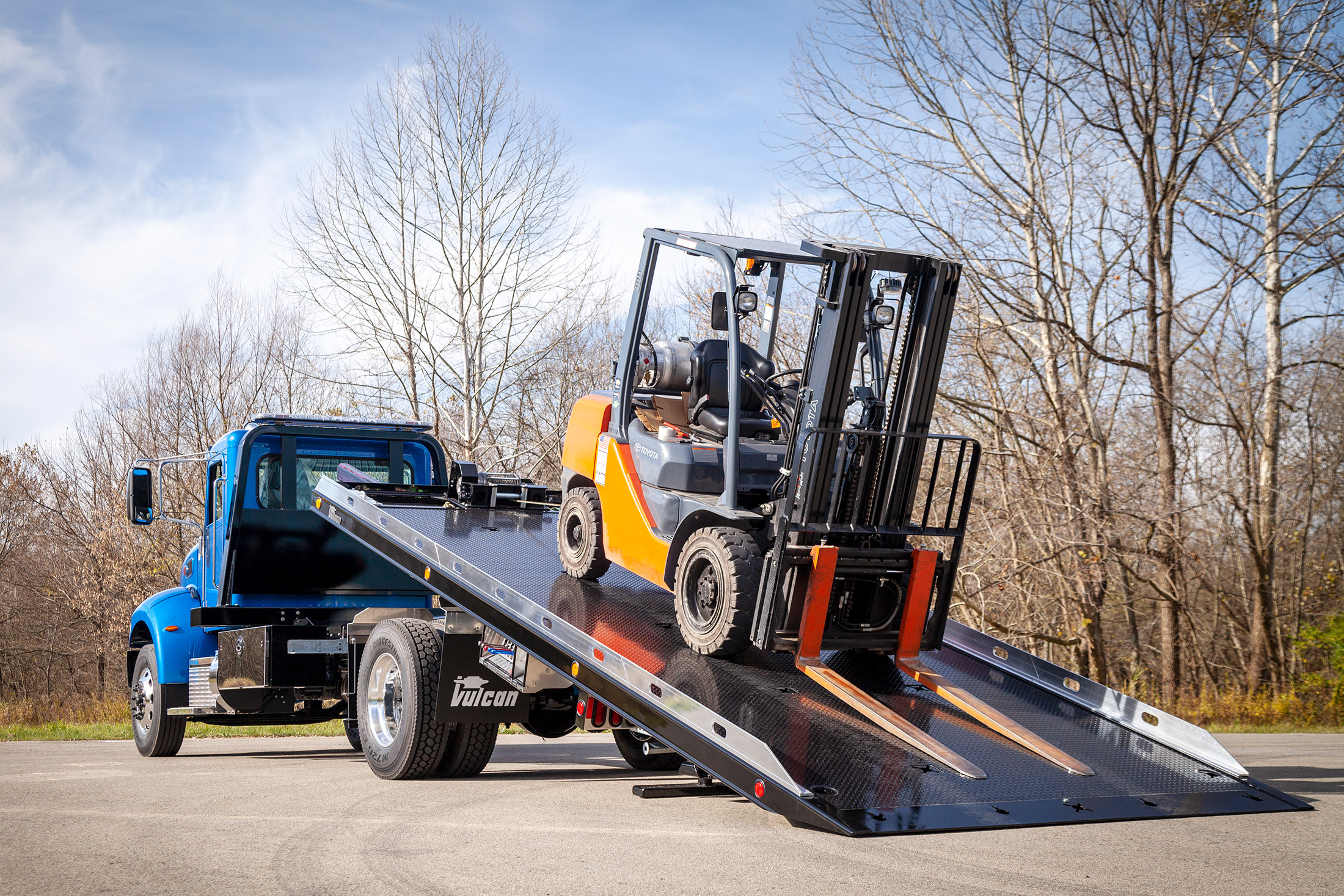 blue Vulcan 16 series lag on a Peterbilt 337 chassis loaded with forklift